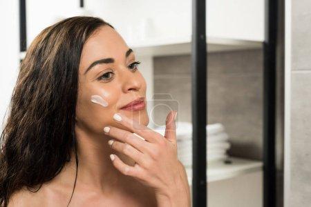 Photo pour Jolie femme appliquant crème visage sur la joue tout en regardant dans le miroir dans la salle de bain - image libre de droit