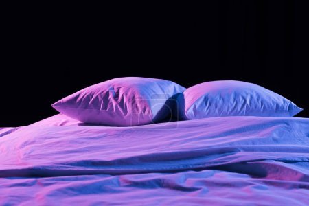 Foto de Blanco almohadas y ropa de cama con luz de neón aislada en negro - Imagen libre de derechos