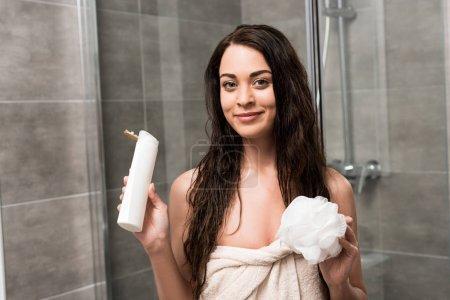 Photo pour Femme brune joyeuse tenant le gel douche et luffa dans mains - image libre de droit