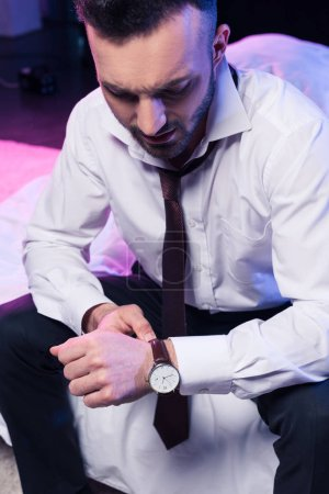 handsome bearded man looking at watch while sitting in suit on bed