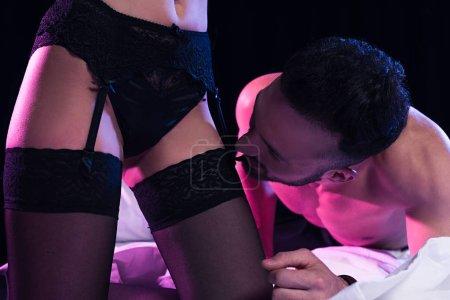 schöner Mann sieht Strümpfe von sexy Frau isoliert auf schwarz
