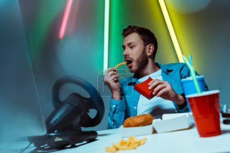 Photo for Good-looking and handsome man eating french fries and looking at computer monitor - Royalty Free Image