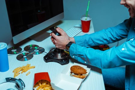 Photo pour Partail view of cyber sportsman holding joystick and playing video game - image libre de droit