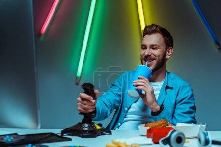 Foto de Hombre guapo sosteniendo el joystick y bebiendo soda de la taza de papel - Imagen libre de derechos
