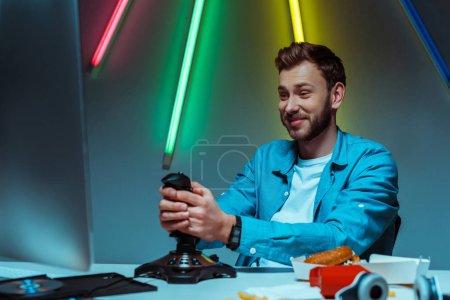 Photo pour Homme beau et souriant jouant le jeu vidéo avec le joystick et regardant le moniteur d'ordinateur - image libre de droit