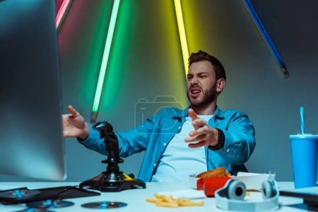 Photo pour Foyer sélectif de l'homme beau et en colère regardant le moniteur d'ordinateur - image libre de droit