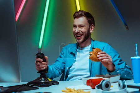 Photo for Handsome and smiling man holding tasty burger and playing video game with joystick - Royalty Free Image