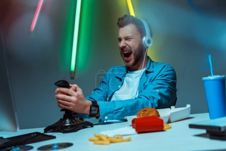 Photo for Selective focus of angry cyber sportsman in headphones playing video game with joystick - Royalty Free Image
