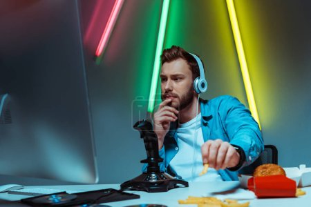 selective focus of handsome cyber man in headphones looking at computer monitor and eating french fries