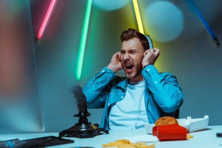 Photo for Angry and handsome cyber sportsman in headphones looking at computer monitor - Royalty Free Image