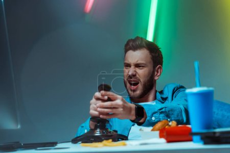Photo for Selective focus of handsome and angry man playing video game with joystick - Royalty Free Image