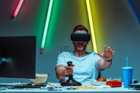 handsome and good-looking man using virtual reality headset and joystick