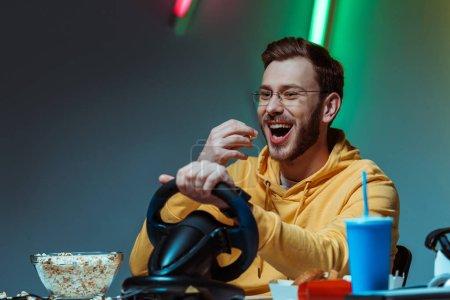Photo pour Homme souriant et beau dans des verres jouant avec le volant et mangeant le popcorn - image libre de droit