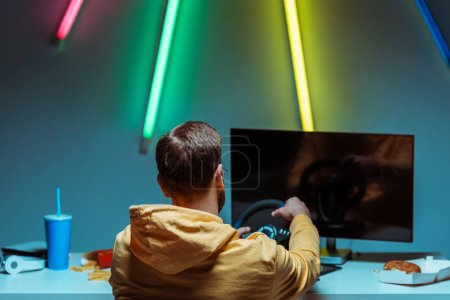 Photo for Back view of man playing video game with steering wheel - Royalty Free Image