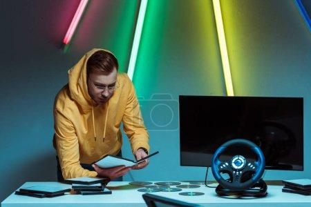 Foto de Hombre guapo y apuesto en gafas de pie y sosteniendo disco compacto con videojuego - Imagen libre de derechos
