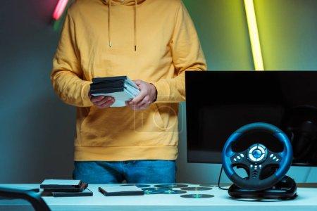 Foto de Vista recortada del hombre de pie y sosteniendo discos compactos con videojuegos - Imagen libre de derechos
