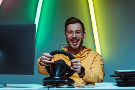 Photo for Smiling, good-looking and handsome man in glasses playing video game with steering wheel - Royalty Free Image