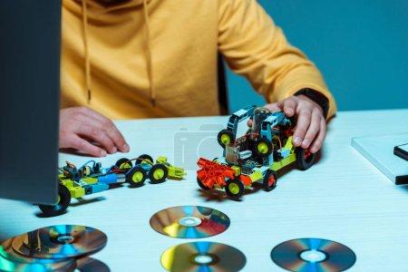 Photo pour Foyer sélectif de l'homme jouant avec la voiture jouet sur la table blanche - image libre de droit