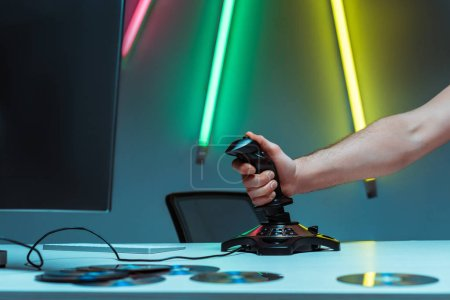 Photo pour Vue partielle de l'homme tenant le joystick sur la table dans l'appartement - image libre de droit