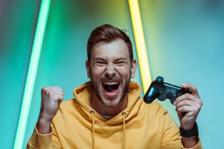 Photo for Handsome and screaming man looking at camera and holding gamepad - Royalty Free Image