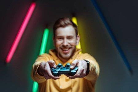 Photo pour Focus sélectif de beau et souriant homme tenant Gamepad - image libre de droit