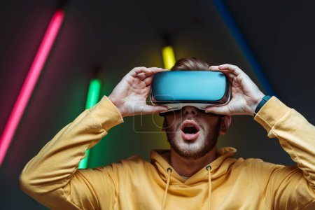 Photo for Surprised young adult and handsome man playing in virtual reality headset - Royalty Free Image