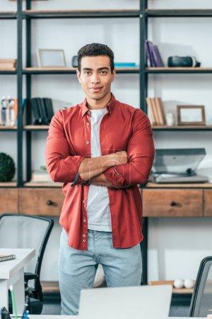 Photo pour Joyeux jeune homme en chemise rouge debout avec les bras croisés sur le lieu de travail - image libre de droit