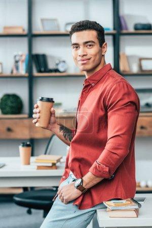 Photo pour Étudiant en chemise rouge tenant une tasse de café en papier - image libre de droit