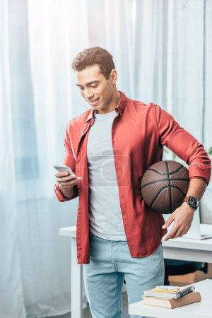 brünetter junger Mann im roten Hemd mit Basketballkorb und Smartphone