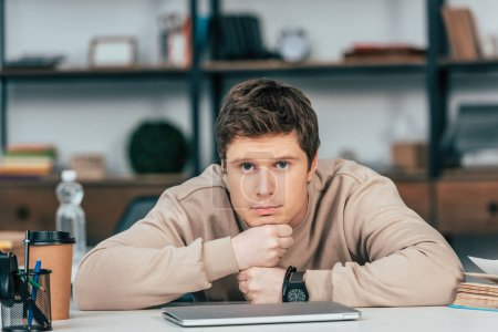 Photo for Upset student in wristwatch sitting with folded arms near laptop and looking at camera - Royalty Free Image