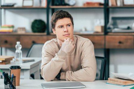 Photo pour Étudiant pensive s'asseyant à la table avec l'ordinateur portatif et le livre - image libre de droit
