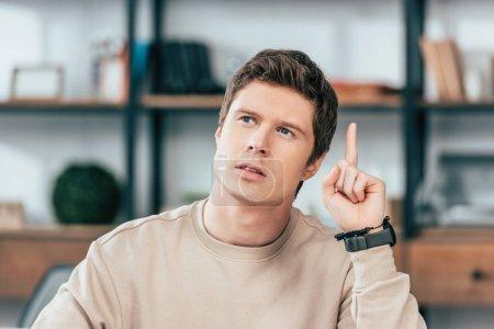 Photo pour Étudiant pensif dans la montre-bracelet regardant vers le haut et pointant du doigt - image libre de droit