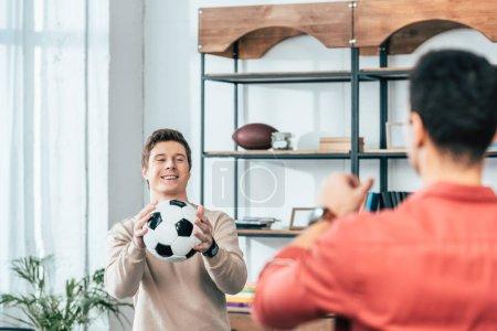 Photo pour Deux amis souriants jouant avec le ballon de football à la maison - image libre de droit