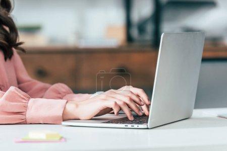 Photo pour Vue recadrée de la fille en chemise rose tapant sur le clavier de l'ordinateur portable - image libre de droit