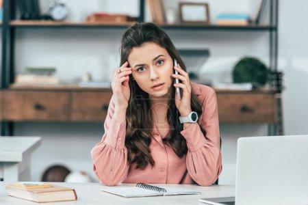 Photo pour Sérieuse jolie fille en chemise rose assise à table et parlant sur smartphone - image libre de droit