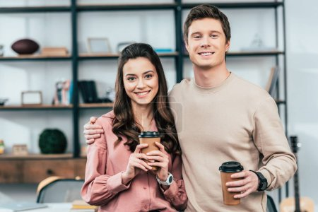 Photo for Two smiling friends holding paper cups of coffee and looking at camera - Royalty Free Image