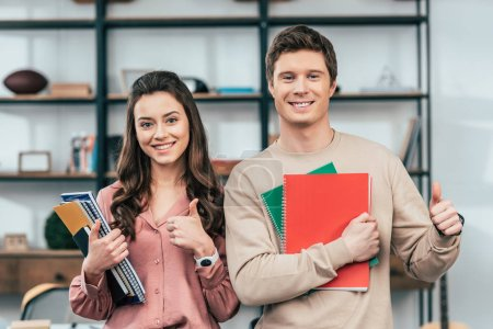 Photo for Two smiling students holding notebooks and showing thumbs up - Royalty Free Image