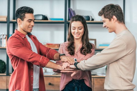 Photo for Three multicultural friends stacking hands together with smile at home - Royalty Free Image