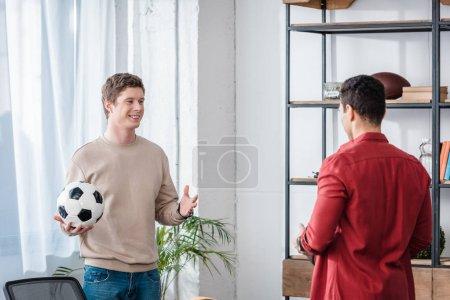 Photo pour Deux amis avec ballon de football parlant avec le sourire à la maison - image libre de droit