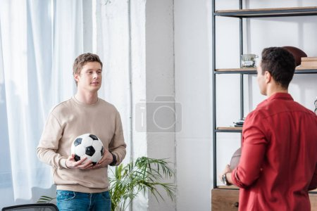 Photo for Two friends with football ball talking with smile at home - Royalty Free Image