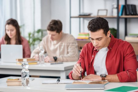 Photo for Concentrated student sitting at desk and reading book in classroom - Royalty Free Image