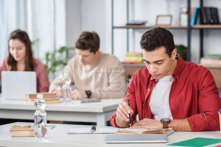 Photo pour Étudiant concentré assis au bureau et lisant un livre en classe - image libre de droit
