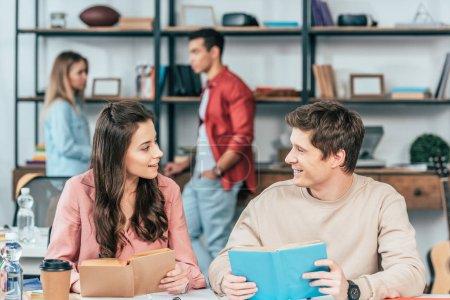 Photo pour Étudiants souriants assis à table avec des livres et se regardant - image libre de droit
