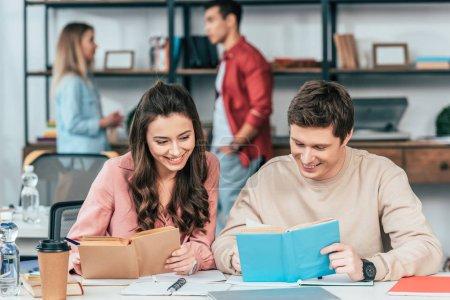 Photo pour Étudiants souriants assis à table et lisant des livres ensemble - image libre de droit