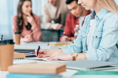 Photo pour Vue recadrée de l'écriture des étudiants dans un carnet de notes en classe - image libre de droit