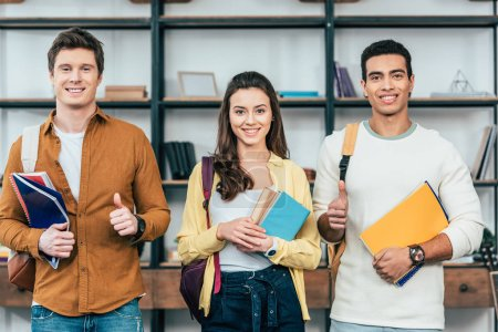 Photo for Three multiethnic happy students holding notebooks and showing thumbs up - Royalty Free Image