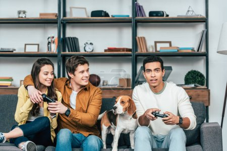 Photo for Three multicultural friends with beagle dog holding joysticks and playing video games - Royalty Free Image
