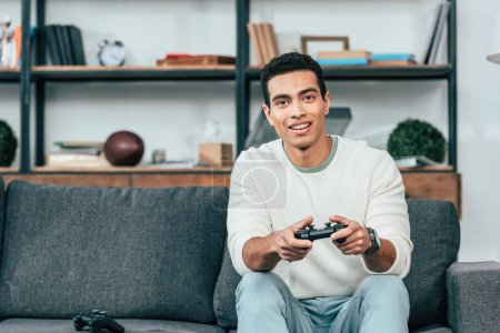 Photo for Joyful young man sitting on sofa and holding gamepad - Royalty Free Image