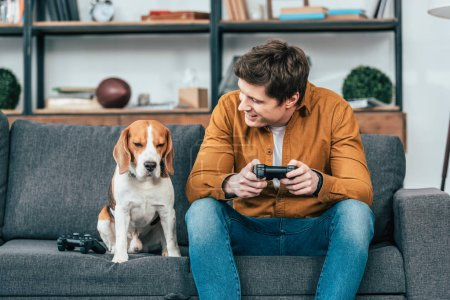 Photo for Smiling young man with gamepad sitting on sofa and looking at dog - Royalty Free Image