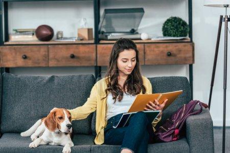 Photo pour Charmant élève lisant le cahier et caressant chien dans le salon - image libre de droit